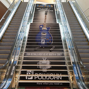 Poly John is using the stairways and escalator for promotional tools with logo and cool graphic of a blue guitar going up the staiirs
