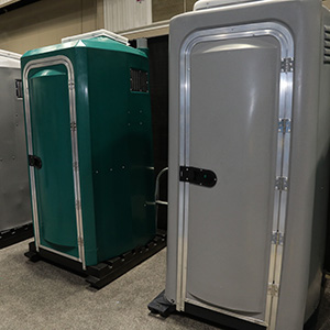 portable restrooms lined up in a row grey and green