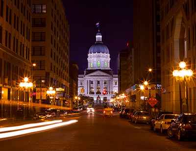 a view of Indiana state capitol at night with sidewalks and street side shops, bars, restaurants