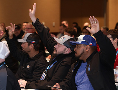 three men in ball caps, in the wastewater industry raising their hands during an education session