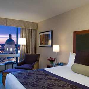 hotel room with clean crisp bed lamp lighting and a large window looking out at the Indiana State Capital Building