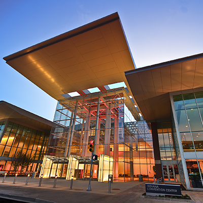 nighttime photo of Indiana Convention Center with climate-controlled walkways and beautiful gold interior lights and modern outdoor directional lights